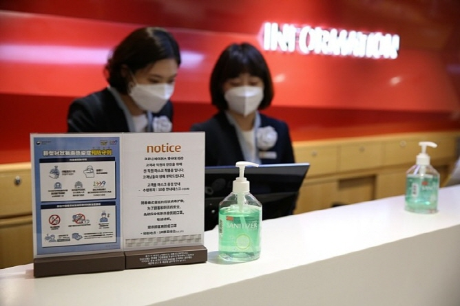 This photo, provided by Lotte Duty Free on Jan. 28 2020, shows its employees wearing facial masks at its outlet in Myeongdong, central Seoul.