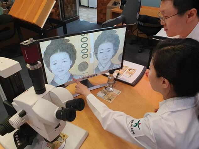 In the photo, provided by KEB Hana Bank, bank officials closely examine a magnified image of what appears to be a fake banknote at a Seoul branch office on Sept. 23, 2019.