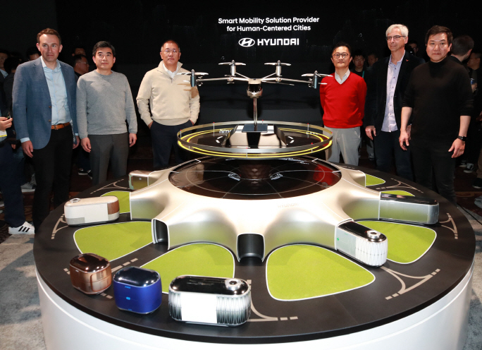 Hyundai Motor Group Executive Vice Chairman Chung Euisun (3rd from left) and Eric Allison, head of Uber's air taxi service Uber Elevate (L), pose with other officials behind the 'S-A1' PAV concept jointly developed by Hyundai and Uber at a CES media day held at Mandalay Bay Hotel in Las Vegas on Jan. 7, 2020 (local time). (image: Hyundai Motor)