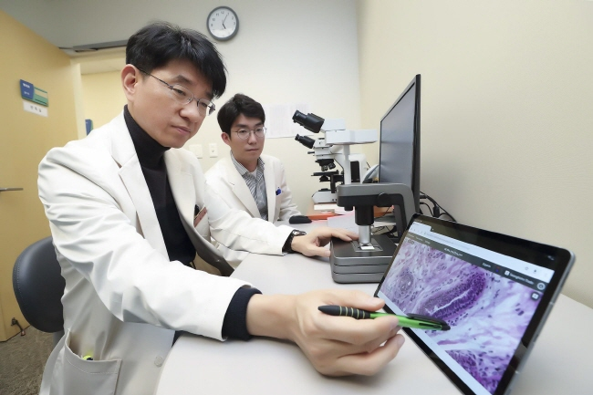 This photo provided by KT Corp. on Jan. 20, 2020, doctors at the Samsung Medical Center in Seoul check pathological data.