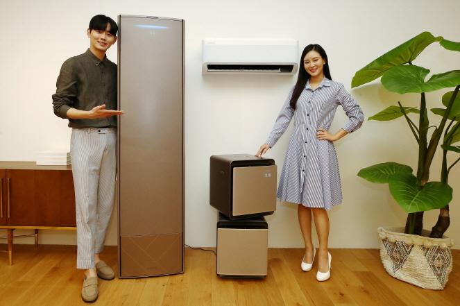Models for Samsung Electronics Co. pose for a photo with the company's new air conditioner (L) and air purifiers at the Samsung Electronics R&D Campus in Seoul on Jan. 15, 2020. (Yonhap)