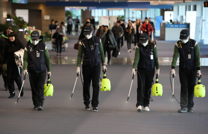 Quarantine workers spray disinfectant at Incheon International Airport, west of Seoul, on Jan. 21, 2020, to prevent the advance of a new strain of coronavirus now spreading in China and other parts of Asia. (Yonhap)