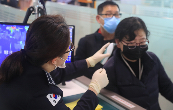 A quarantine officer at Jeju Airport uses an electronic thermometer to check the temperature of passengers. (Yonhap)