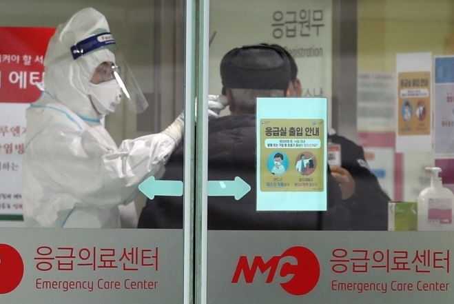 Staff at the National Medical Center in downtown Seoul check the temperature of a person entering its emergency care center on Jan. 27, 2020, as South Korea reported its fourth case of the China coronavirus. (Yonhap)