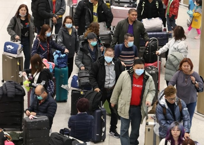 Foreign tourists wearing masks arrive at Incheon International Airport, west of Seoul, on Jan. 27, 2020. (Yonhap)