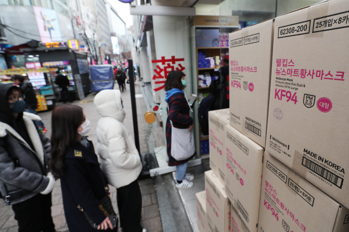 People assumed to be foreign tourists queue at a pharmacy in Myeongdong in central Seoul to buy masks on Jan. 27, 2020. (Yonhap)