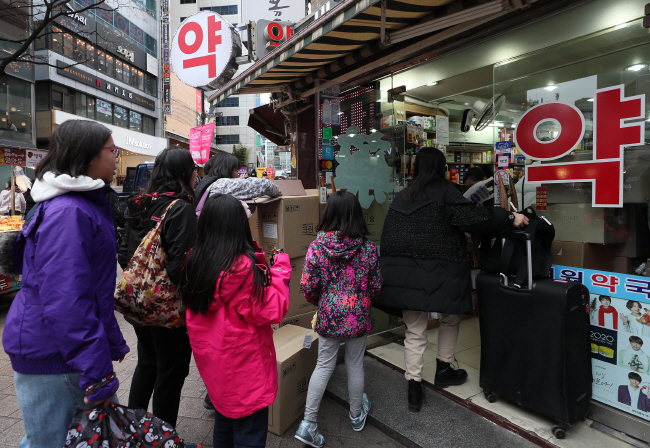 Foreign tourists line up to purchase facial masks at a drug store in Myeongdong, central Seoul, on Jan. 27, 2020. (Yonhap)