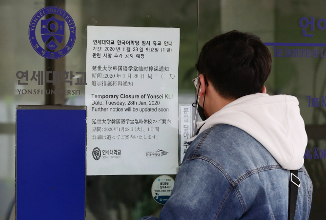 A student reads a public notice at Yonsei University, western Seoul, announcing the temporary closure of the school's Korea Language Institute on Jan. 29, 2020. (Yonhap)