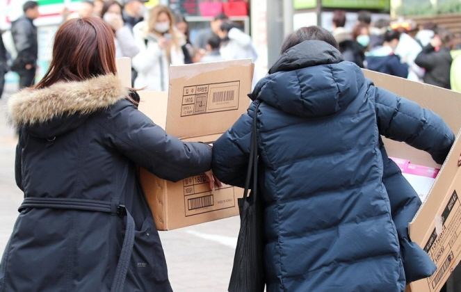 A group of Chinese visitors carry boxes of face masks purchased from a drug store in Myeongdong, central Seoul, on Jan. 31, 2020. (Yonhap)