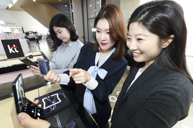 This photo provided by KT Corp. on Feb. 14, 2020, shows people checking Samsung Electronics Co.'s latest foldable phone, the Galaxy Z Flip, at a KT store in Seoul.