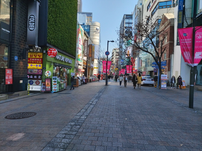 A few people walk on a street in Myeongdong in downtown Seoul on Feb. 9, 2020. The normally busy tourist district was nearly empty amid growing fears of the new coronavirus. (Yonhap)