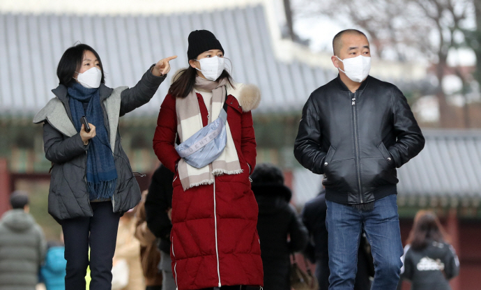 Tourists wearing masks visit an ancient palace in central Seoul on Jan. 28, 2020, amid growing concerns over the spread of the new deadly coronavirus that originated in China. (Yonhap)