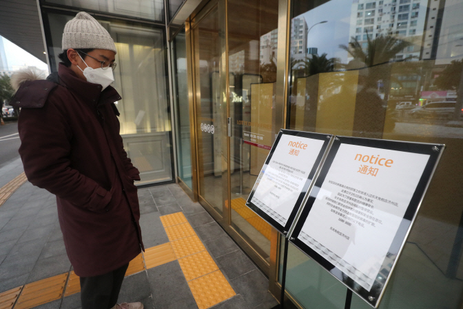 A visitor reads a notice of closure at a duty free shop on South Korea's southern resort island of Jeju on Feb. 2, 2020. (Yonhap)