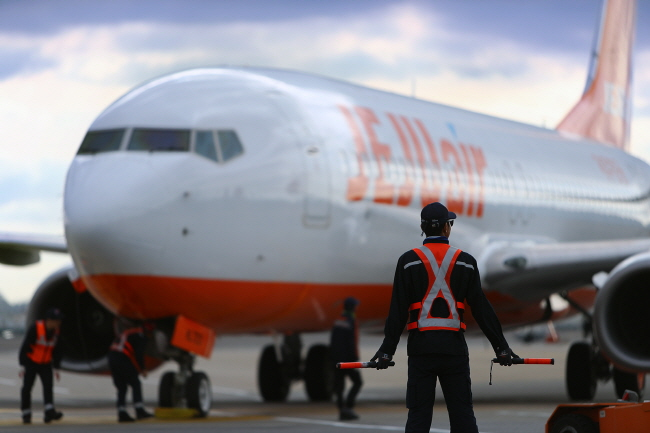 This photo taken on Feb. 3, 2020, and provided by Jeju Air shows airport personnel preparing quarantine work for passengers on an arriving airplane at Jeju International Airport.