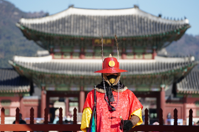 A guard wearing a mask with a goblin-pattern embroidery stands in front of Gwanghwamun on Feb. 6, 2020, in this file photo. (Yonhap)