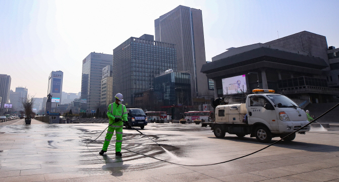 Officials from the Jongno Ward Office disinfect Gwanghwamun Square in central Seoul in an effort to contain the new coronavirus. (Yonhap)