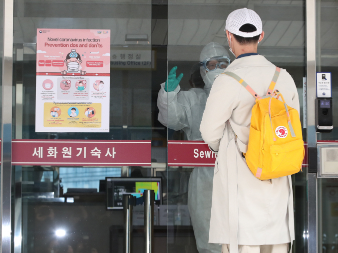 A Chinese student listens to a quarantine official before entering a dormitory building of Kyunghee University in eastern Seoul on Feb. 24, 2020. (Yonhap)