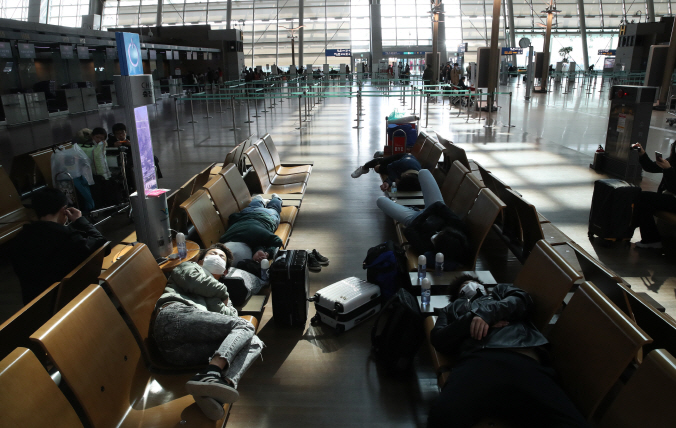 This photo taken on Feb. 26, 2020, shows Incheon International Airport with foreign tourists in masks resting on seats amid the spreading coronavirus outbreak. (Yonhap)