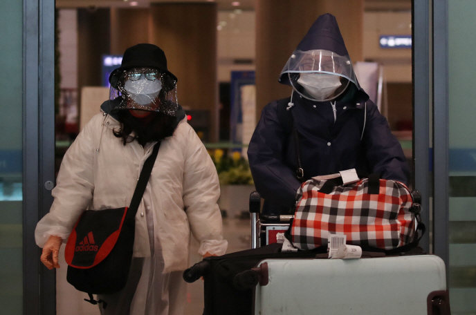 Chinese tourists wearing masks and visors enter the country via Incheon International Airport on Feb. 26, 2020. (Yonhap)