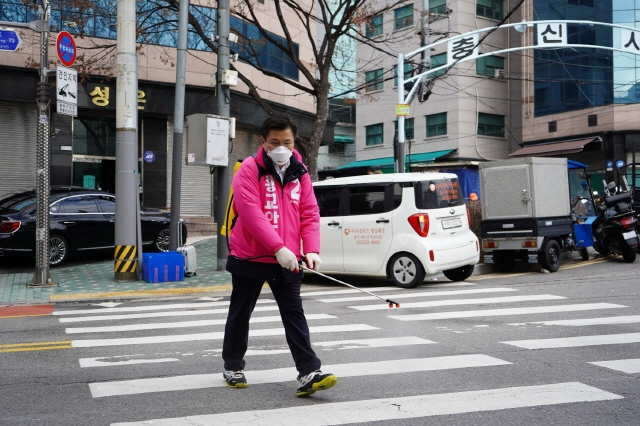 Hwang Kyo-ahn, chief of the main opposition United Future Party, disinfects a street to help contain the new coronavirus in Jongno in central Seoul on Feb. 26, 2020, in this photo provided by his aides. (Yonhap)