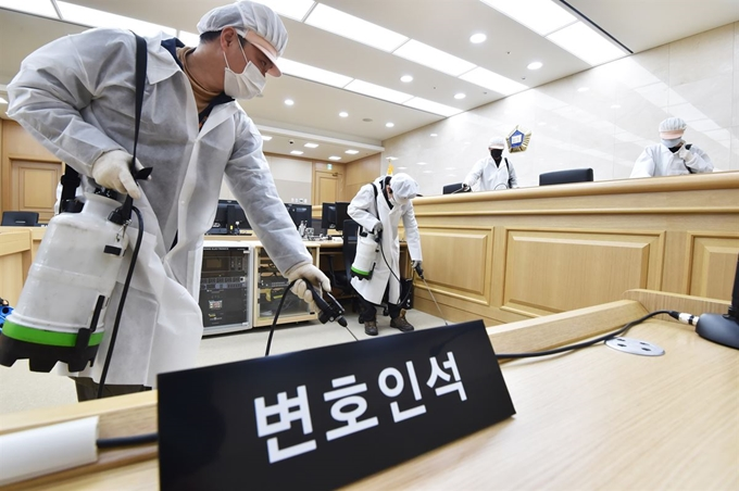 Health workers disinfect a court room in Suwon, Gyeonggi Province on March 1, 2020, as South Korea struggles to prevent the spread of the novel coronavirus. (Yonhap)