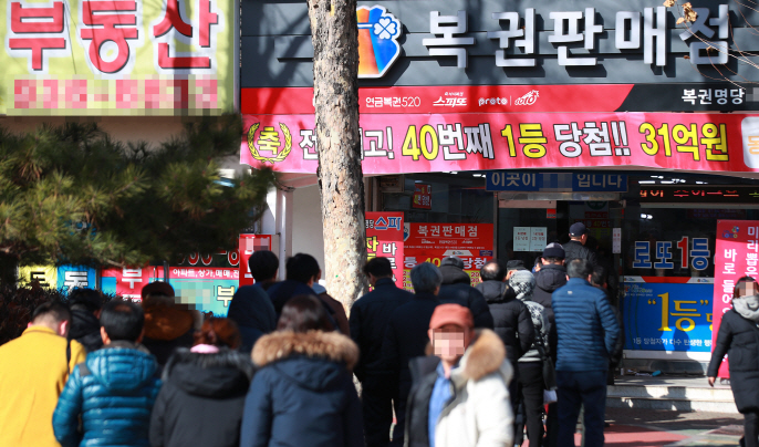 This undated file photo shows people queuing in front of a sales outlet in Seoul to buy Lotto tickets. (Yonhap)