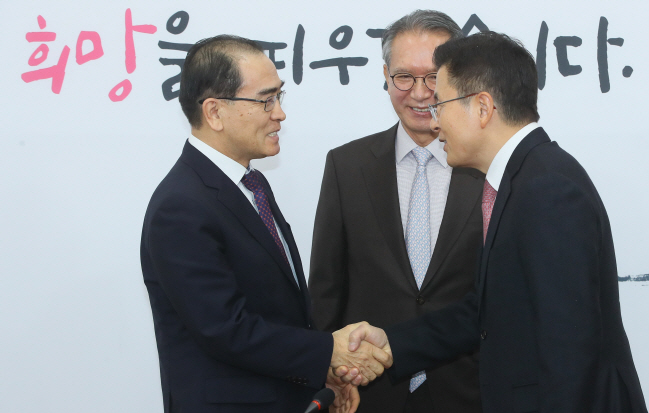 Hwang Kyo-ahn (R), chairman of the main opposition Liberty Korea Party (LKP), shakes hands with Thae Yong-ho, a former ranking North Korean diplomat who defected to South Korea in 2016, after Thae declared that he will run for the April 15 general elections on the LKP ticket, at the National Assembly in Seoul on Feb. 11, 2020. (Yonhap)