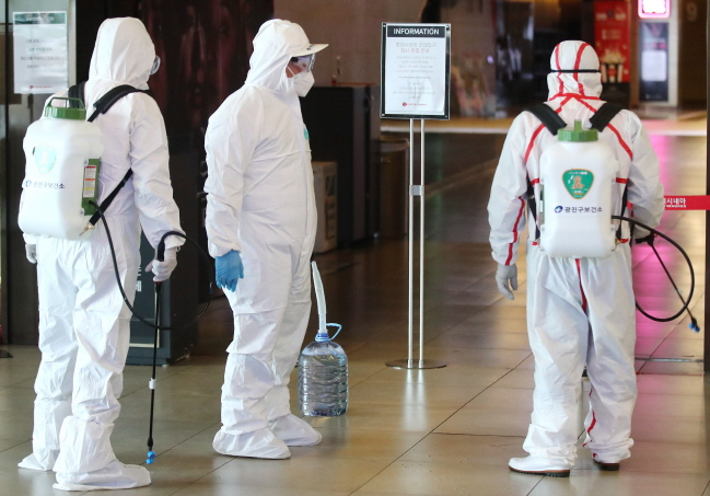 Seoul public health workers disinfect Lotte Cinema cineplex near Konkuk University in Seoul on Feb. 26, 2020. (Yonhap)