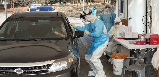 A medical worker collects a sample from a citizen in an automobile at a drive-through clinic in Cheonan, 90 kilometers south of Seoul, on Feb. 29, 2020, to test for the new coronavirus. (Yonhap)