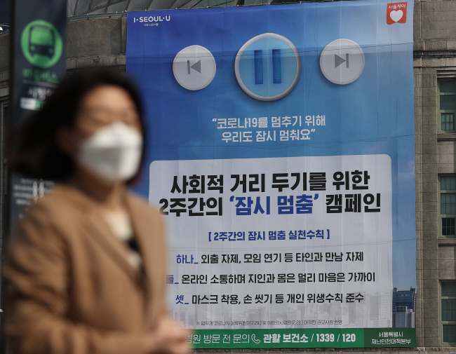 A citizen walking past a social-distancing campaign poster in Seoul. (Yonhap)