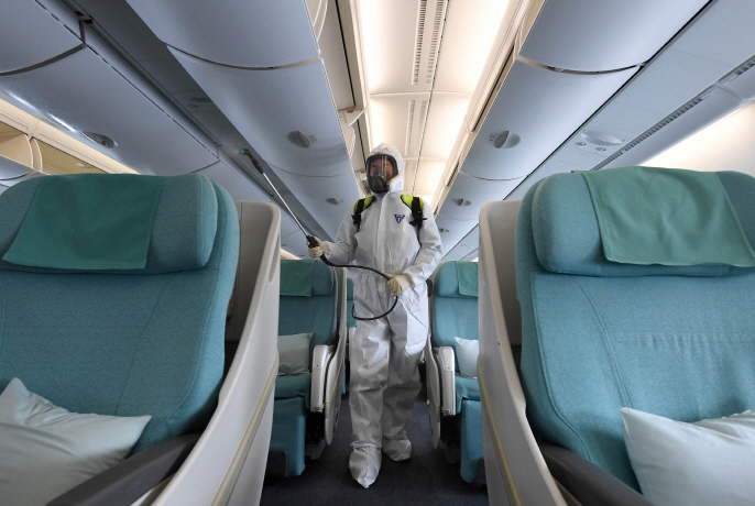 A health worker disinfects the cabin of a Korean Air Lines Co. aircraft at Incheon International Airport in Incheon, west of Seoul, in this file photo taken on March 4, 2020. (Yonhap)