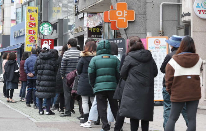 People form a long queue outside a pharmacy in in Ulsan, 414 kilometers southeast of Seoul, on March 9, 2020, as they wait to purchase face masks amid the spread of the new coronavirus. (Yonhap)