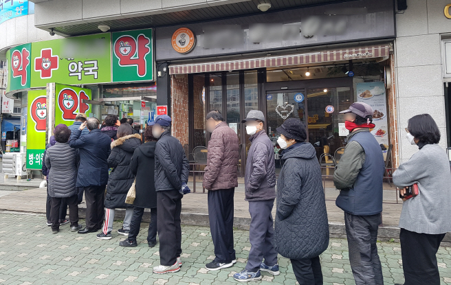 People wait in a line to buy masks at a pharmacy in the southeastern port city of Busan on March 9, 2020, the first day of the government's new mask rationing system. (Yonhap)