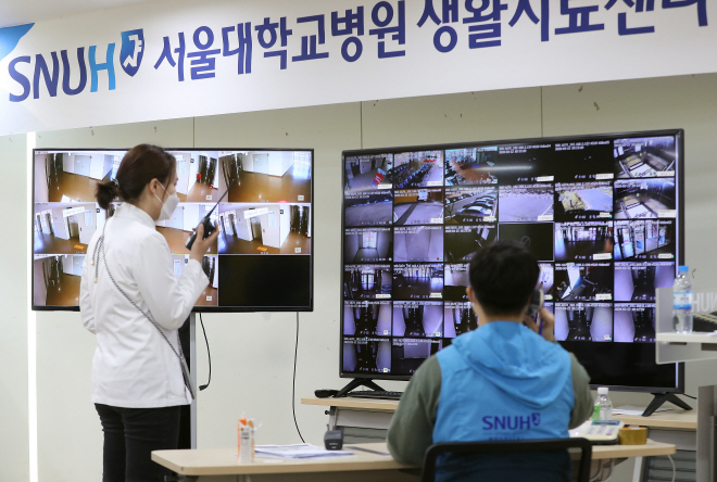 Medical staff at a community treatment center in Mungyeong, 180 kilometers southeast of Seoul, monitor COVID-19 patients quarantined at the facility on March 12, 2020. (Yonhap)