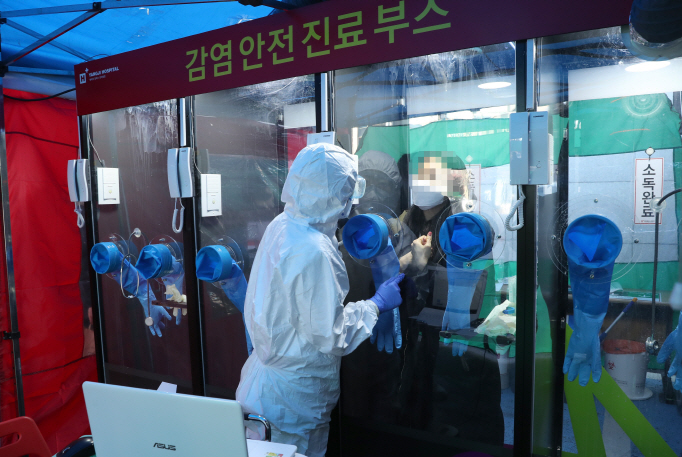 "A medical worker takes a sample from a woman to test for the new coronavirus at a ""walk-through"" testing facility at a hospital in Seoul on March 16, 2020. (Yonhap)"
