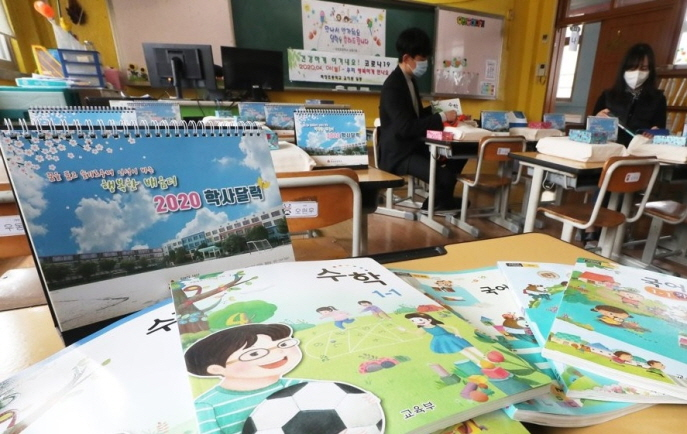 Teachers sort out textbooks and gifts for would-be first graders at a classroom of Pajang Elementary School in Suwon, south of Seoul, on March 17, 2020. (Yonhap)