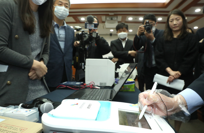 Wearing a plastic glove, an official of the National Election Commission, demonstrates how to cast a ballot for early voting amid the nationwide coronavirus outbreak at the commission's headquarters in Gwacheon, south of Seoul, on March 17, 2020. (Yonhap)