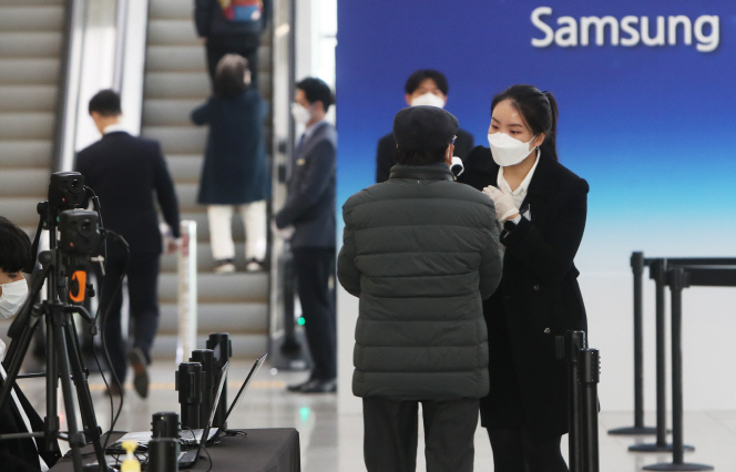 A shareholder of Samsung Electronics Co. receives a temperature check before entering the company's shareholder meeting at a convention center in Suwon, south of Seoul, on March 18, 2020. (Yonhap)