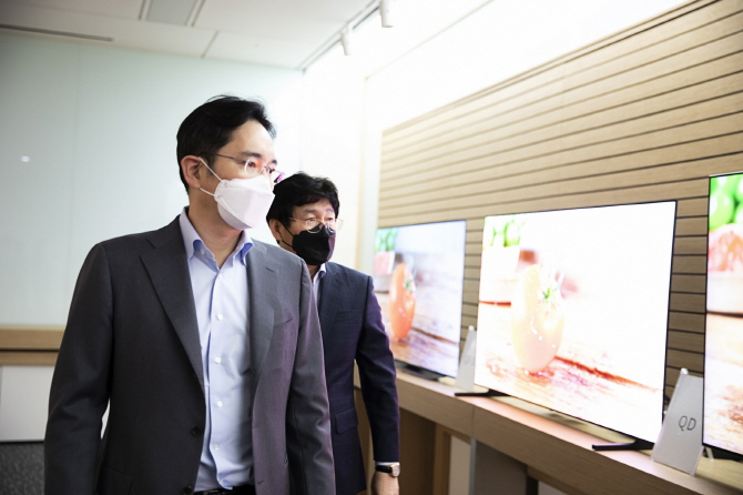 In this photo provided by Samsung Electronics Co. on March 19, 2020, Samsung Electronics Vice Chairman Lee Jae-yong (L) inspects Samsung Display Co.'s products at the company's plant in Asan, south of Seoul.