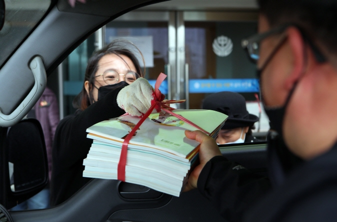 A driver picks up textbooks for his child in his car from a teacher at Yeongcheon Middle School in Yeongcheon, North Gyeongsang Province, on March 19, 2020, amid the spread of the new coronavirus. (Yonhap)