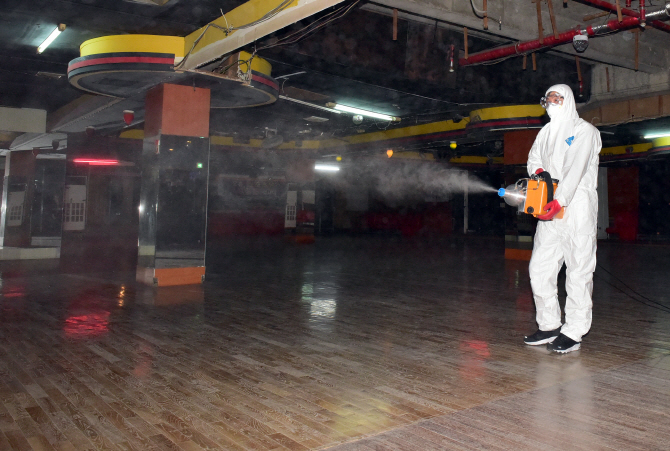 This photo, provided by the office of the Busanjin Ward in the southeastern city of Busan on March 19, 2020, shows a quarantine official disinfecting an alcohol-free dance club over the new coronavirus.