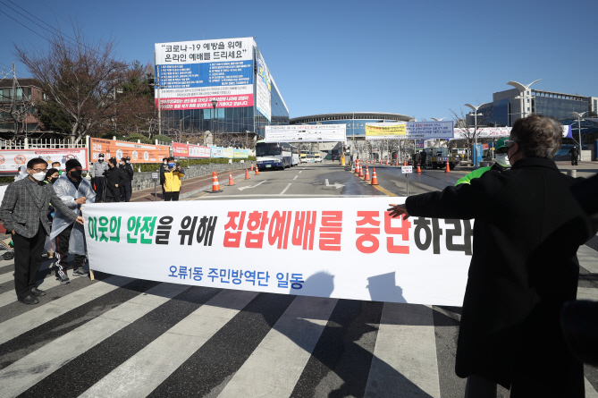 Residents of the Oryu-1 neighborhood in southwestern Seoul hold a protest rally in front of a Protestant church in their neighborhood that went ahead with a Sunday service on March 22, 2020. (Yonhap)