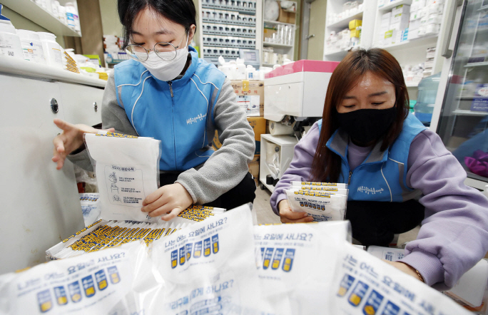 Volunteer workers package protective masks at a pharmacy in the southeastern city of Gwangju on March 23, 2020, in this photo provided by the Buk-gu district office in the city.