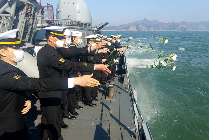 Sailors aboard the 2nd Naval Fleet's patrol ship Hwang Do-hyeon offer flowers in waters off the northern border island of Baeknyeong on March 23, 2020. (Yonhap)