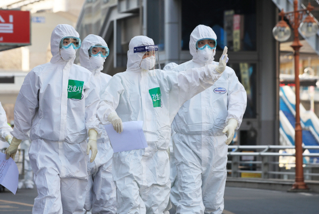 Medical staffers wave to reporters while entering Dongsan Hospital in the virus-hit city of Daegu for a work shift on March 24, 2020. (Yonhap)