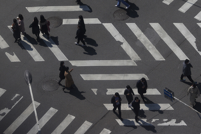 People cross a street junction in Seoul on March 24, 2020. (Yonhap)