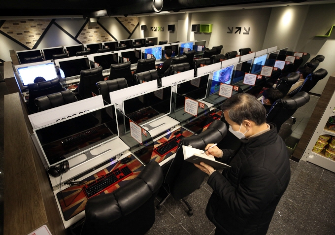 """A civil servant inspects the quarantine measures taken at an internet cafe, or """"PC bang,"""" in Daegu, amid the novel coronavirus outbreak on March 24, 2020. (Yonhap)"""