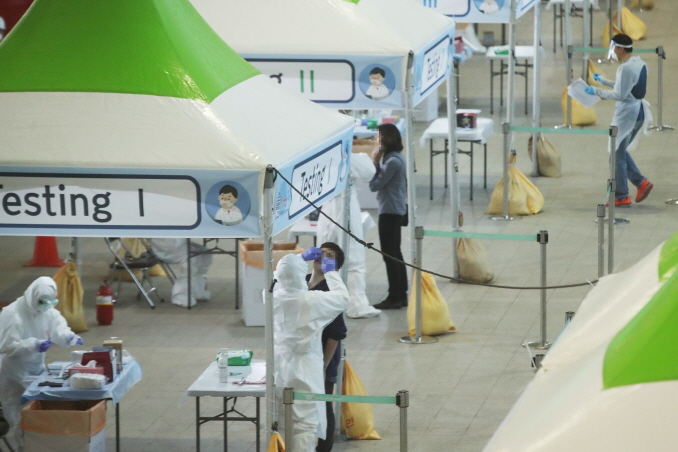 Passengers from Europe undergo COVID-19 tests at a walk-through clinic set up outside Incheon International Airport, west of Seoul, on March 26, 2020. (Yonhap)