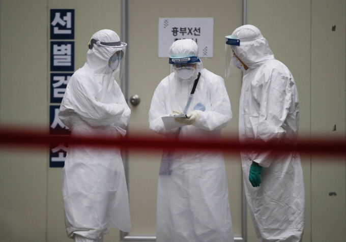 Medical workers in protective gear make preparations in front of a testing facility at a hospital in the virus-hit city of Daegu on March 26, 2020. (Yonhap)