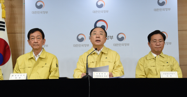 Finance Minister Hong Nam-ki (C) makes an announcement about an aid package for virus-hit families in a news conference in Seoul on March 30, 2020. (image: Ministry of Finance and Economy)